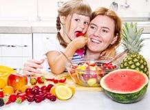 母亲给小女孩水果沙拉在厨房里 库存照片