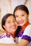 母亲美丽的画象有女儿的,佩带的传统安地斯山的衣裳和配比的项链,摆在 免版税库存图片