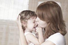 母亲舒适哭泣的女婴 免版税库存照片