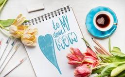 母亲节与在上写字对我亲爱的妈妈的文本的贺卡、俏丽的郁金香、笔记本或者写生簿、五颜六色的刷子标志和c 库存图片