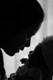 母亲节与新出生的婴孩护理的接合概念 母亲是使用和谈话与在窗口旁边的新出生的婴孩 库存照片