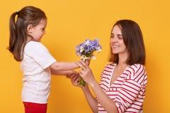 母亲节快乐!儿童女儿祝贺妈妈并且给她的花束 妈咪佩带的镶边衬衣和女孩 免版税图库摄影