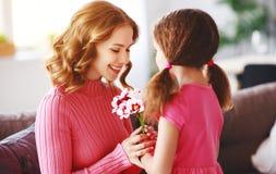 母亲节快乐!儿童女儿给母亲一花束郁金香和明信片 免版税库存照片