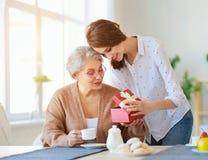 母亲节快乐!成人女儿在度假给礼物并且祝贺一个年长母亲 库存照片