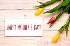 母亲节快乐,与郁金香的问候在土气板条 库存照片