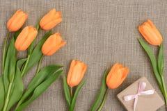 母亲节背景 郁金香,在麻袋布的礼物 免版税库存图片
