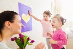 母亲节,给花和卡片的女孩他们的妈咪 库存照片