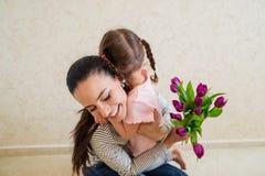 母亲节,给花的小女孩她的妈咪 免版税库存图片