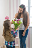 母亲节-女孩给她的妈妈郁金香大花束,接触 免版税图库摄影