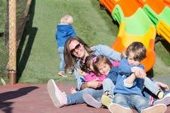 母亲获得与孩子的乐趣在操场 库存照片