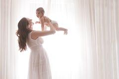 母亲藏品由空白窗帘的小儿子 免版税图库摄影