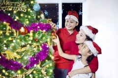 母亲装饰与她的孩子的一棵圣诞树 免版税库存图片