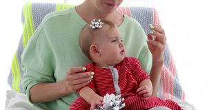 母亲装饰有包装的弓的婴孩的头 股票录像