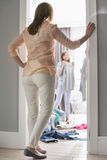 母亲观看的女儿全长背面图尝试在衣裳的在屋子里 免版税库存照片
