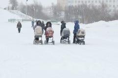 年轻母亲走与在暴风雪的婴儿推车 库存照片