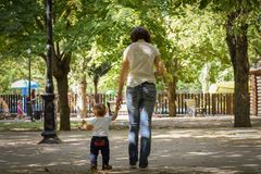 母亲走与她的握他的手的孩子在秋天公园 负责任的父母身分概念 库存照片