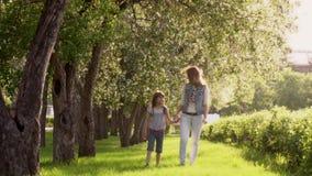 母亲走与她的沿苹果树大道的女儿  小女孩由手拿着她的母亲 孩子