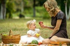 母亲走与孩子在庭院里在夏天 免版税库存照片