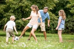 母亲踢与家庭的橄榄球足球 免版税图库摄影