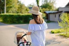 年轻母亲身怀婴儿推车的一个孩子 库存照片