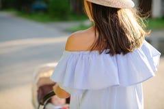 年轻母亲身怀婴儿推车的一个孩子 图库摄影