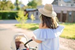 年轻母亲身怀婴儿推车的一个孩子 库存图片