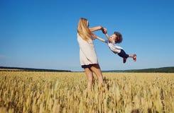 母亲转动一个孩子获得在自然的乐趣在夏天 免版税库存图片