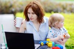 年轻母亲运转的哦膝上型计算机和拿着她的儿子 免版税库存照片
