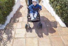 母亲运载在台阶下的一辆婴儿推车,不用舷梯 库存照片
