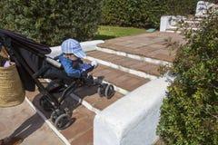 母亲运载在台阶下的一辆婴儿推车,不用舷梯 免版税库存照片