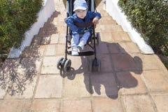 母亲运载在台阶下的一辆婴儿推车,不用舷梯 免版税库存图片