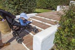 母亲运载在台阶下的一辆婴儿推车,不用舷梯 免版税图库摄影