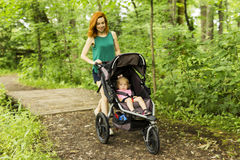 母亲采取一辆婴儿推车的婴孩在途中 库存照片