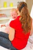 母亲镇定的哭泣的婴孩 免版税库存照片