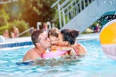 母亲,亲吻游泳池的父亲女儿 晴朗的夏天 免版税库存图片