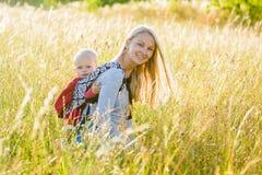 母亲,女儿在草甸 免版税图库摄影