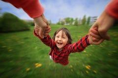 母亲,转动在圈子她的小男婴,纯净的喜悦,辐形 免版税库存照片