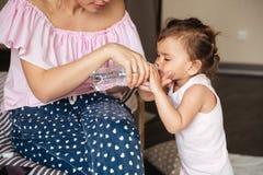 母亲给一个瓶水她的小女儿 图库摄影