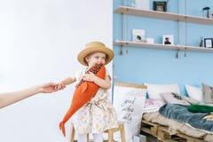 母亲给一只手小女儿 坐椅子和在家拿着一条玩具鱼的小女孩在屋子里 免版税库存图片