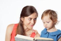 母亲读与她的女儿的一本书 免版税库存图片