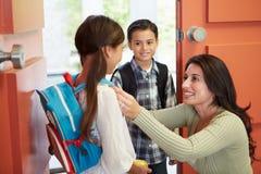 母亲说再见向孩子,他们为学校离开