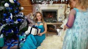 母亲给她的女儿一件礼物,圣诞节礼物,美妙地包装在有弓的包装纸箱子,礼物在下 股票视频