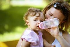 母亲给她的孩子从瓶的饮料水 免版税图库摄影