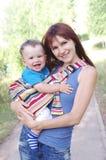 母亲婴孩吊索的carrys儿子 免版税图库摄影