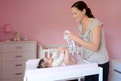 年轻母亲更换在她的婴孩的衣裳 免版税库存照片