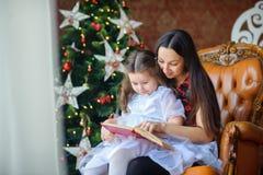 母亲读童话给小女儿 免版税库存图片
