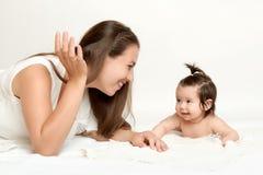 母亲画象和婴孩在白色毛巾说谎 库存照片