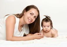 母亲画象和婴孩在白色毛巾说谎 免版税库存照片