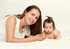 母亲画象和婴孩在白色毛巾说谎 库存图片