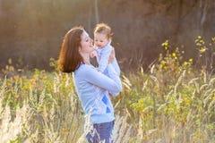 母亲画象有她新出生的婴孩的在晴朗的公园 免版税库存图片